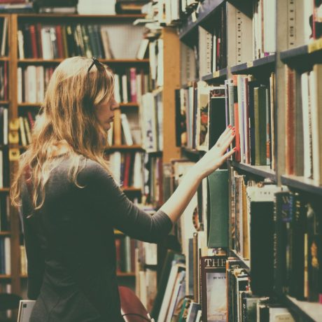 woman-in-black-long-sleeved-looking-for-books-in-library-926680